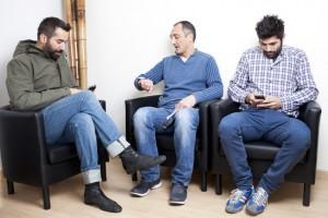 Drei Personen warten beim Arzt