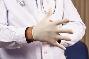 Arzt zieht sich Handschuh an